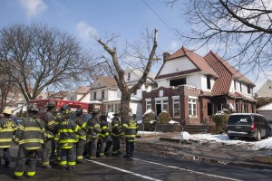 Firefighters stand outside the home hours after it caught fire. (Reuters/Stephanie Keith)