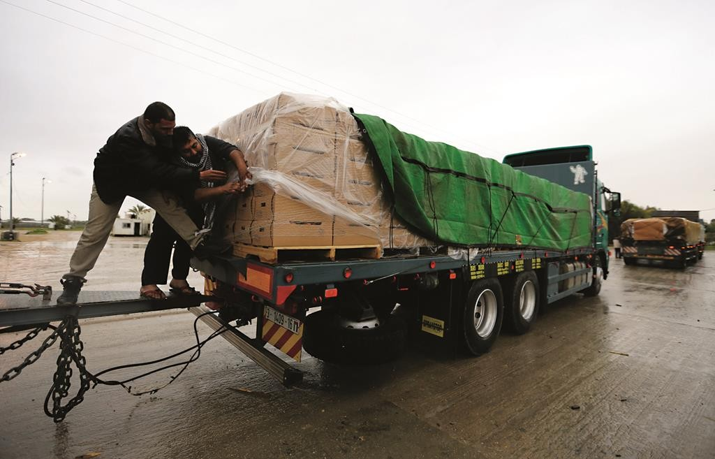 Palestinians covering cartons containing vegetables before exporting them to Israel, Thursday, at the Kerem Shalom crossing in the Gaza Strip.  (REUTERS/Ibraheem Abu Mustafa - IDF Photo)