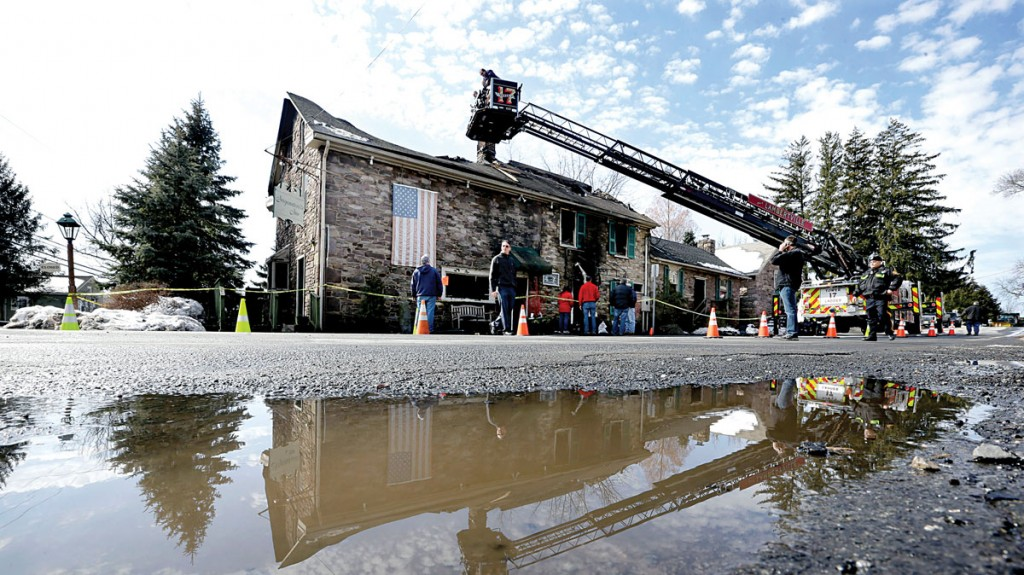Firefighters and officials on Monday investigate an overnight fire that destroyed The Sergeantsville Inn in Delaware Township, N.J. (AP Photo/Mel Evans)