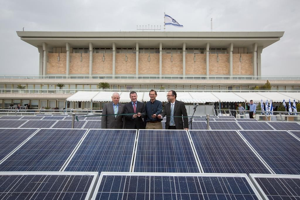 Speaker of the Knesset Yuli Edelstein cuts the ribbon at an inauguration ceremony for solar panels on the roof of the Israeli parliament. The 4,650-square-yard field is the largest set of solar panels on any parliament in the world.  (Miriam Alster/FLASH90)