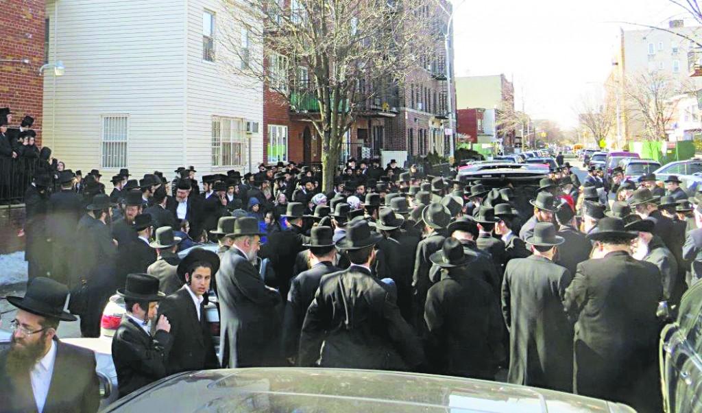 (Top) The levayah of the Kavanas Halev Rebbetzin on Friday in front of the beis medrash. (Bottom) The Kavanas Halev Rebbe at his Rebbetzin's levayah. (JDN)