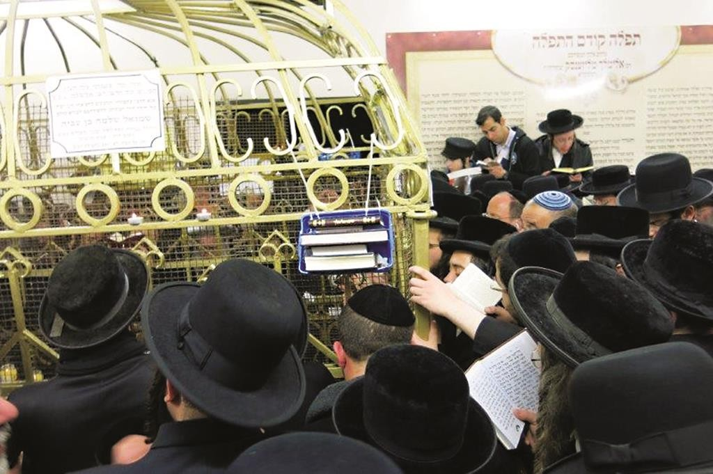 """Davening at the tziyun of the Rebbe Reb Elimelech, zy""""a."""