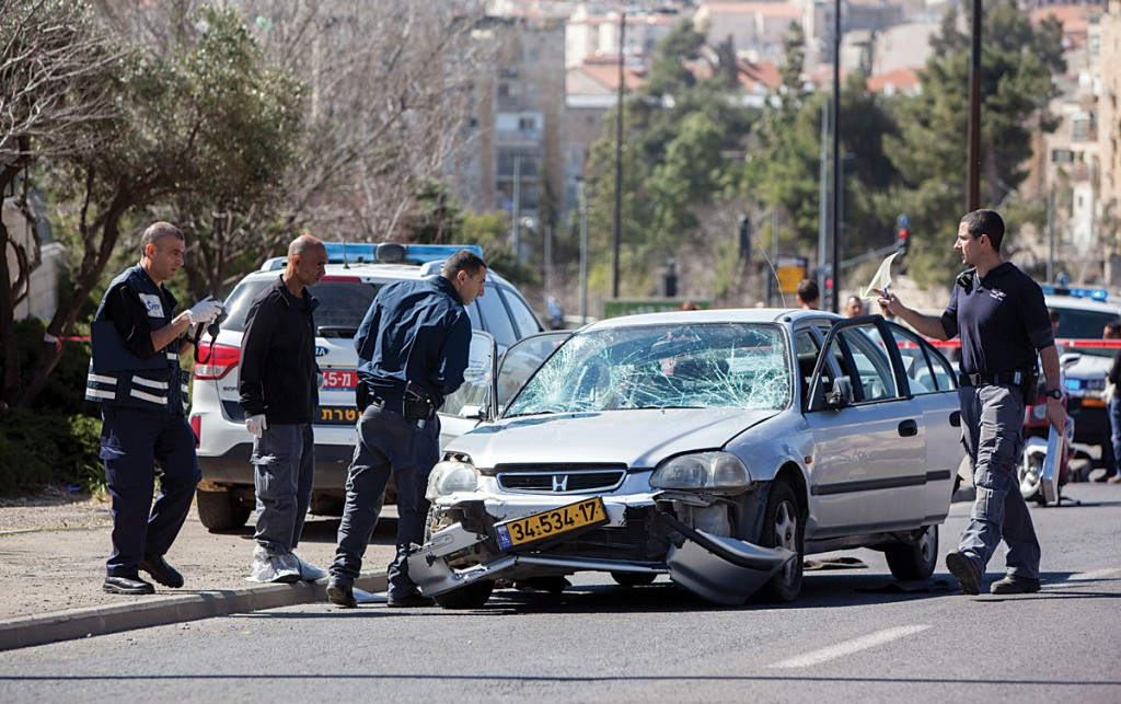 Israeli police inspecting a car at the scene of a terror attack in Yerushalayim in which five people were injured. (Yonatan Sindel/Flash90)