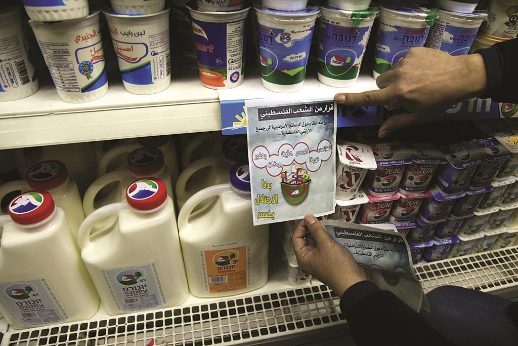 A Palestinian activist places a sign to boycott Israeli products at a supermarket in Beit Lechem. (AP Photo/Mahmoud Illean)