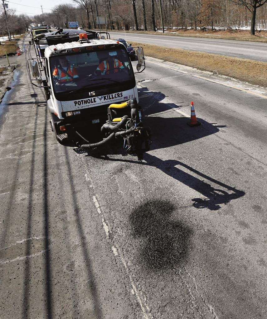 New Jersey transportation workers on Monday use a special truck to fill and repair potholes during a demonstration in Hamilton Township, N.J. (AP Photo/Mel Evans)