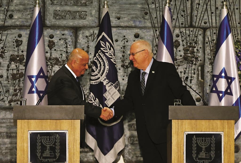 Central Elections Committee Chairman Judge Salim Joubran (L) shakes hands with Israel's President Reuven Rivlin during a handover ceremony of the official March 17, election results in Yerushalayim on Wednesday. (REUTERS/Ammar Awad)