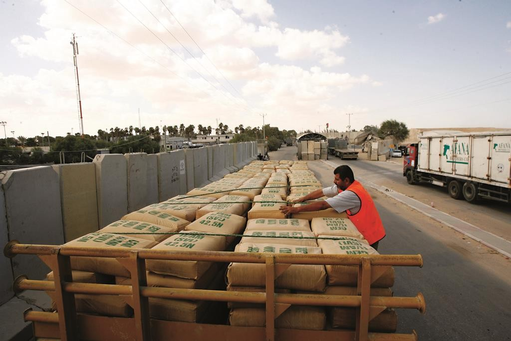A Palestinian worker checking a truck loaded with cement bags after it entered the Gaza Strip through the Kerem Shalom crossing. (Abed Rahim Khatib/Flash90)