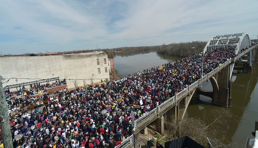Crowds of people take a symbolic walk across the Edmund Pettus Bridge, Sunday, in Selma, Ala. (AP Photo/Bill Frakes)