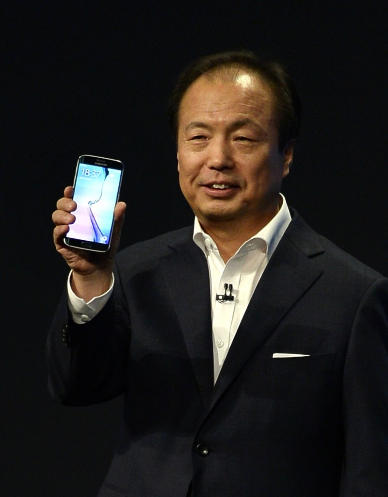 JK Shin, CEO of Samsung's mobile division, shows the new Galaxy S6 during a Samsung Galaxy Unpacked 2015 event on the eve of this week's Mobile World Congress wireless show, in Barcelona, Spain, Sunday, March 1, 2015. Samsung unveiled a stylish new flagship phone that ditches its signature plastic design for metal and glass. The South Korean phone manufacturer also unveiled a premium model with a display that curves around the left and right edges so that information can be quickly glanced at on the side. (AP Photo/Manu Fernandez)