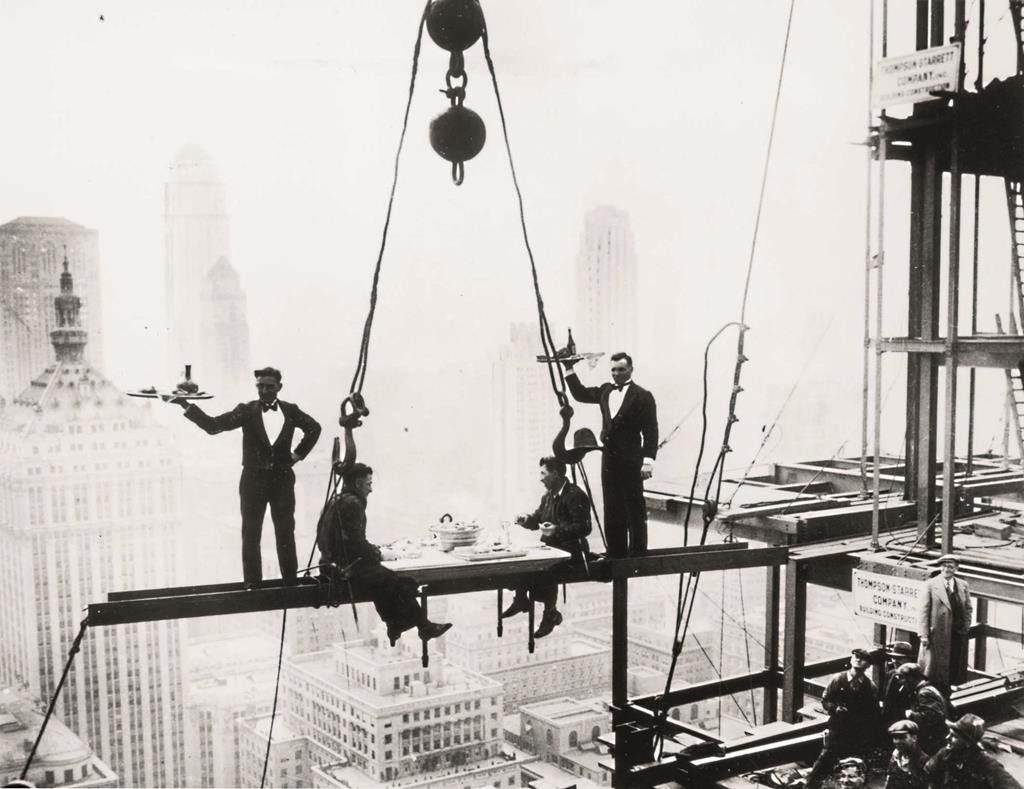 Waiters serve two workers lunch on a girder high above Manhattan in this Nov. 14, 1930, photo of the building of the Waldorf-Astoria Hotel. Just getting there adds hours to the workweek. (Keystone/Getty Images)