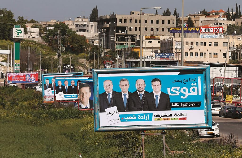 Campaign billboards for the Joint Arab List line the road in the Arab Israeli town of Arabe. Israel's Arab minority is uniting under one banner for the first time in the coming election. Surveys show the Joint Arab List could even finish third in the vote and become a factor in the coalition-building. (REUTERS/Ammar Awad)