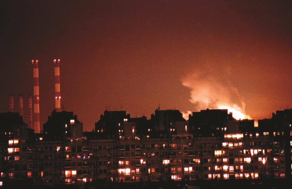 Flames from an explosion light up the Belgrade skyline near a power station, left, after NATO cruise missiles and warplanes attacked Yugoslavia late Wednesday, March 24, 1999. (AP Photo/Dimitri Messinis)