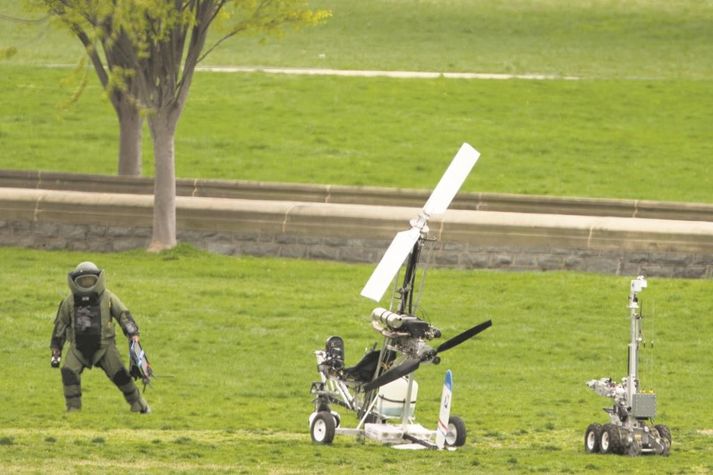 A member of a bomb squad approaches a small helicopter after it landed on the West Lawn of the Capitol in Washington, Wednesday. (AP Photo/Andrew Harnik)
