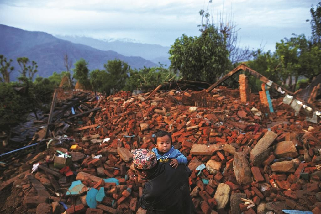 A local villager walks carrying a child amid debris in Gorkha, Nepal, April 28, 2015.  (REUTERS/Athit Perawongmetha)