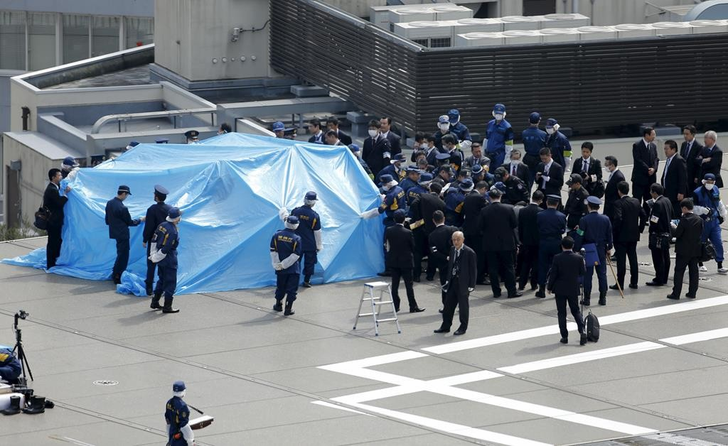 Police and security officials stand around a tarpaulin covering a drone on the roof of Prime Minister Shinzo Abe's official residence in Tokyo, Wednesday. (REUTERS/Toru Hanai)