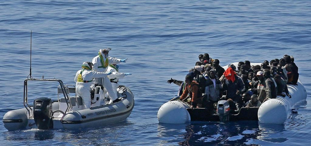 In this photo made available Thursday migrants crowd an inflatable dinghy as a rescue vessel of the Italian Coast Guard approaches them off the Libyan coast, in the Mediterranean Sea, Wednesday, April 22. (Alessandro Di Meo/ANSA via AP Photo)