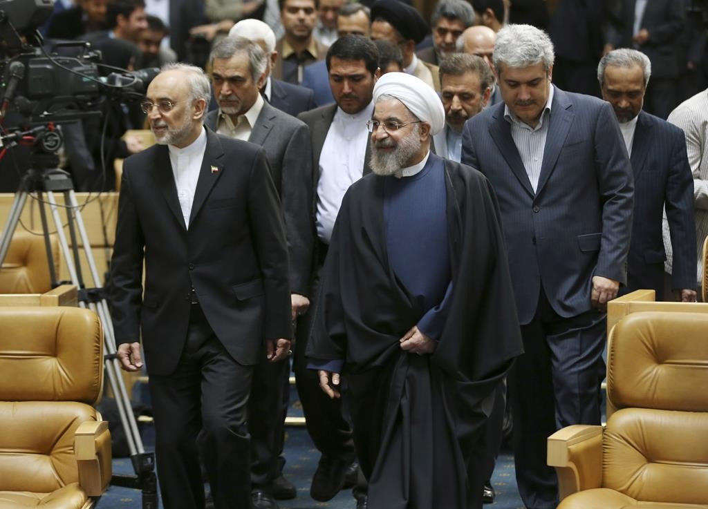 Iranian President Hassan Rouhani, center, arrives to attend a ceremony marking National Nuclear Technology Day, as he is accompanied by head of Iran's Atomic Energy Organization Ali Akbar Salehi, left, and Vice President for science and technology affairs Sorena Sattari, right, in Tehran, Iran, Thursday, April 9, 2015. Rouhani warned that Tehran will not sign on to a final nuclear deal with world powers unless it is predicated on the lifting of economic sanctions imposed on Iran over the controversial nuclear program.  (AP Photo/Vahid Salemi)