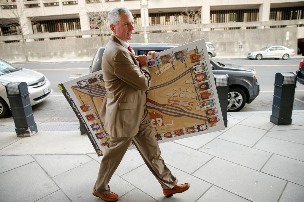 "A man carrying a poster that reads ""approximate locations of victims around Nisoor Square"" enters the E. Barrett Prettyman Federal Courthouse in Washington, Monday, for a sentencing hearing for four former Blackwater security guards in connection with a 2007 shooting of civilians in Nisoor Square, Baghdad. (AP Photo/Andrew Harnik)"