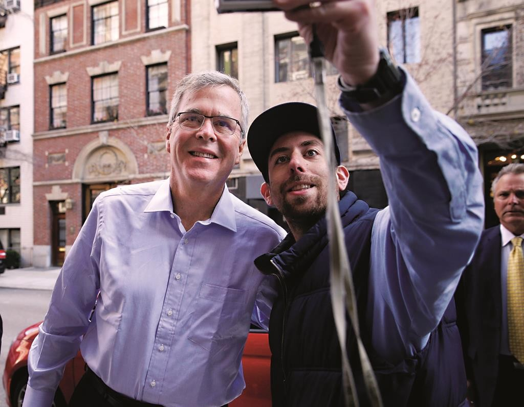 Former Florida Gov, Jeb Bush on Thursday takes a picture with Jason Ertischek as he arrives to an event in New York. (AP Photo/Seth Wenig)