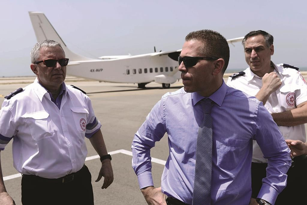 Minister of Internal Affairs Gilad Erdan (C) waiting to greet Israelis who survived the massive earthquake that killed thousands in Nepal a few days ago, as the survivors arrive at Sde Dov Airport in Tel Aviv on a Magen David Adom aircraft. (Tomer Neuberg/FLASH90)