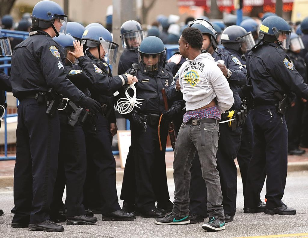 Police detain a man after a march to City Hall for Freddie Gray, Saturday, April 25, in Baltimore.  (AP Photo/Alex Brandon)