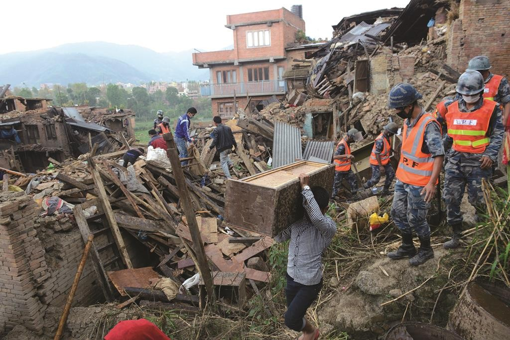 People carry their belongings amidst the rubble of collapsed houses in Bhaktapur, on the outskirts of Kathmandu, on Monday, April 27, two days after a 7.8 magnitude earthquake hit Nepal. (Prakash Mathema/AFP/Getty Images)