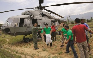 Nepalese volunteers unload relief material brought in an Indian air force helicopter Monday for victims of Saturday's earthquake. (AP Photo/Altaf Qadri)