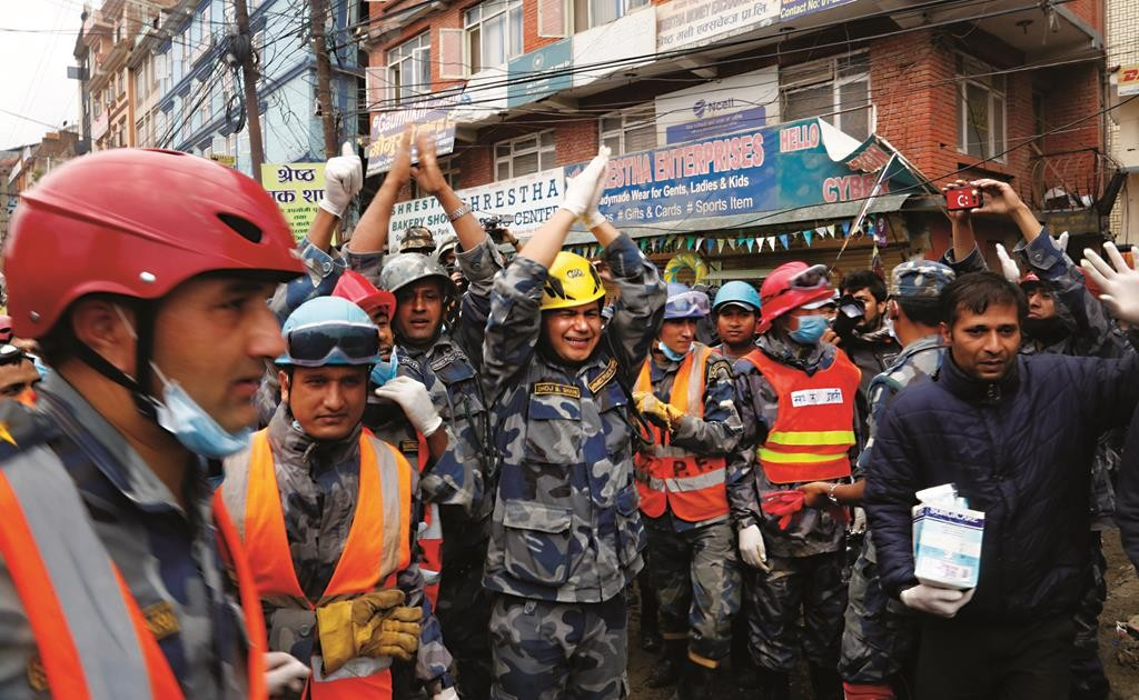 Nepalese policemen cheer after they, along with U.S. rescuers, pulled out Pemba Tamang, a teenage boy from a building that collapsed five days ago in Kathmandu, Nepal, Thursday. (AP Photo / Manish Swarup)
