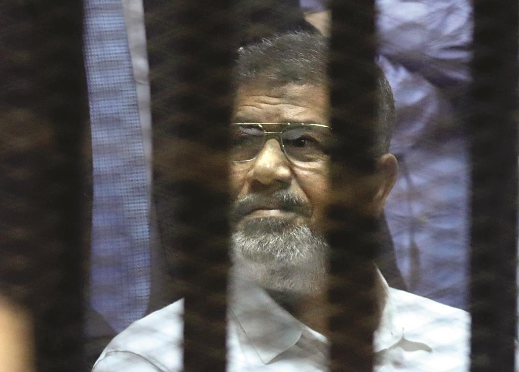 Egypt's ousted Islamist former president Mohammed Morsi sits in a soundproof glass cage inside a makeshift courtroom at Egypt's national police academy in Cairo, Egypt, Tuesday. (AP Photo/Amr Nabil)