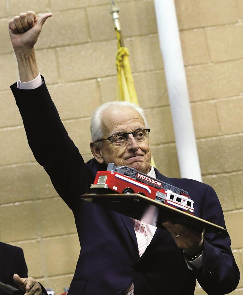 Rep. Bill Pascrell, a former mayor of Paterson, holds up a plaque with a fire truck given to him during ceremonies opening a new fire headquarters. (AP Photo/Mel Evans)