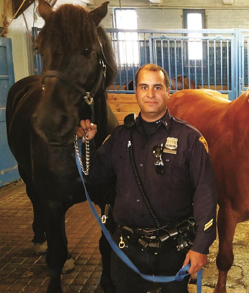 Officer Luis Ramos stands with horse Pompey II at the NYPD stable. (NYPD)