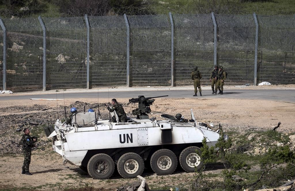 Israeli soldiers (right) and members of United Nations peacekeeping forces seen near the frontier with Syria near Majdel Shams in the Golan Heights on Monday. (REUTERS/Baz Ratner)