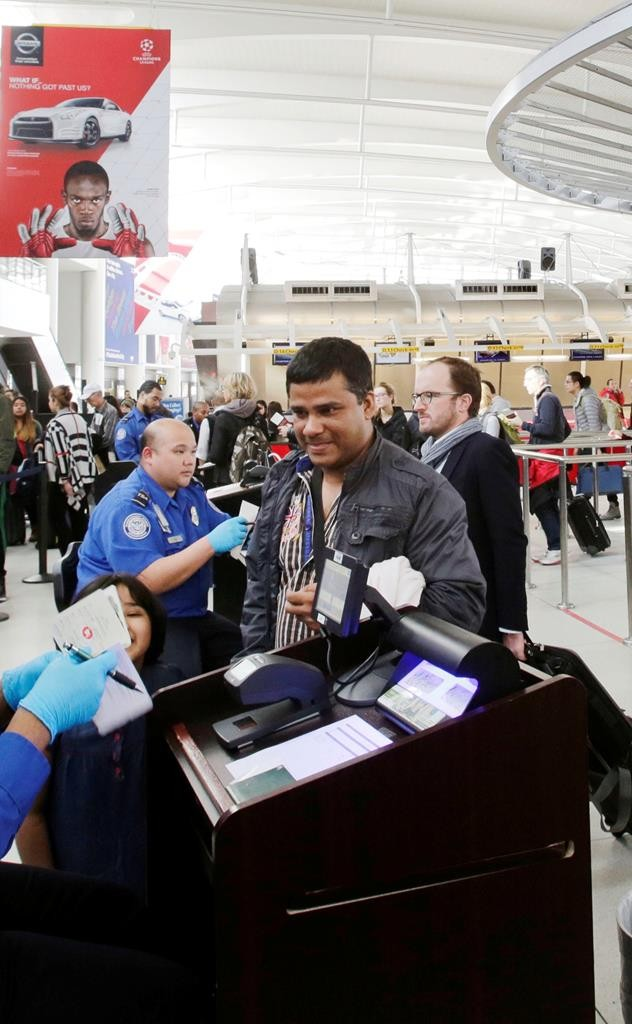 A TSA officer, left, checks a passenger's ticket, boarding pass and passport as part of security screening at John F. Kennedy International Airport in New York.  (AP Photo/Mark Lennihan)