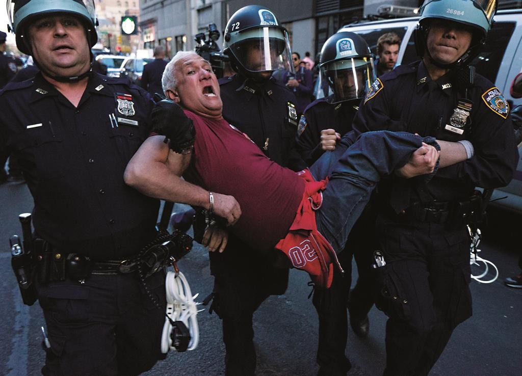 A man is carried by police officers as arrests are made at Union Square late Wednesday. (AP Photo/Craig Ruttle)
