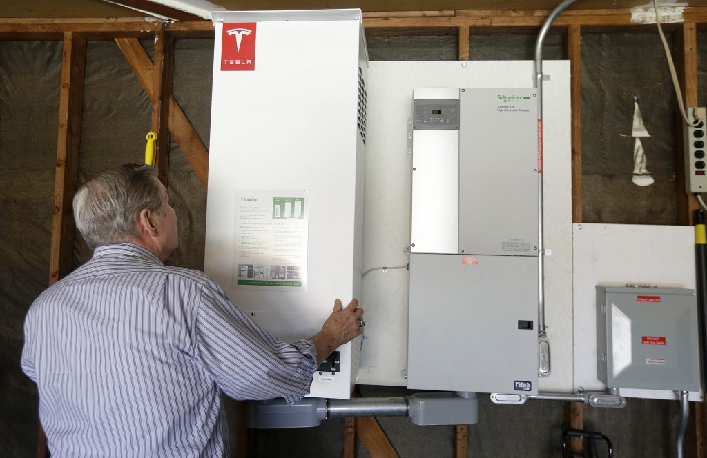David Cunningham shows a prototype Tesla battery system that powers his Foster City, Calif., home, on April 20, 2015. Cunningham installed the battery late last year to pair with his solar panels as part of a pilot program run by the California Public Utilities Commission to test home battery performance. Tesla was expected to unveil a stationary battery for homeowners and businesses on Thursday, April 30, 2015. (AP Photo/Jeff Chiu)
