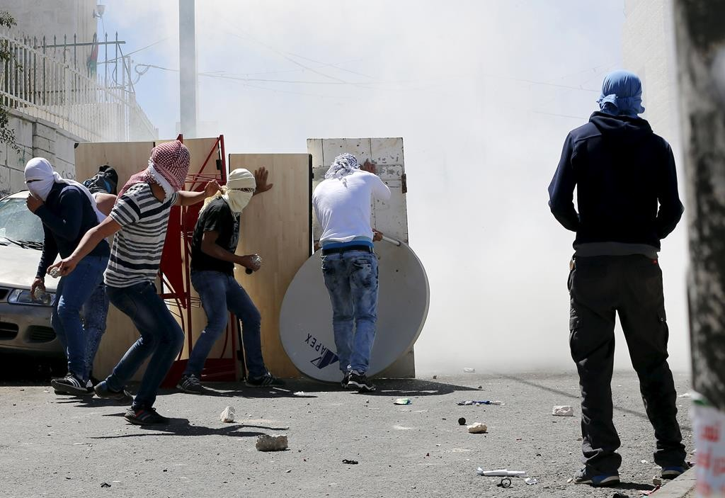 Palestinian youths throwing stones at Israeli police during clashes in the eastern Yerushalayim neighborhood of A-tur, after a Palestinian youth was killed by Israeli security forces.  (REUTERS/Ammar Awad)
