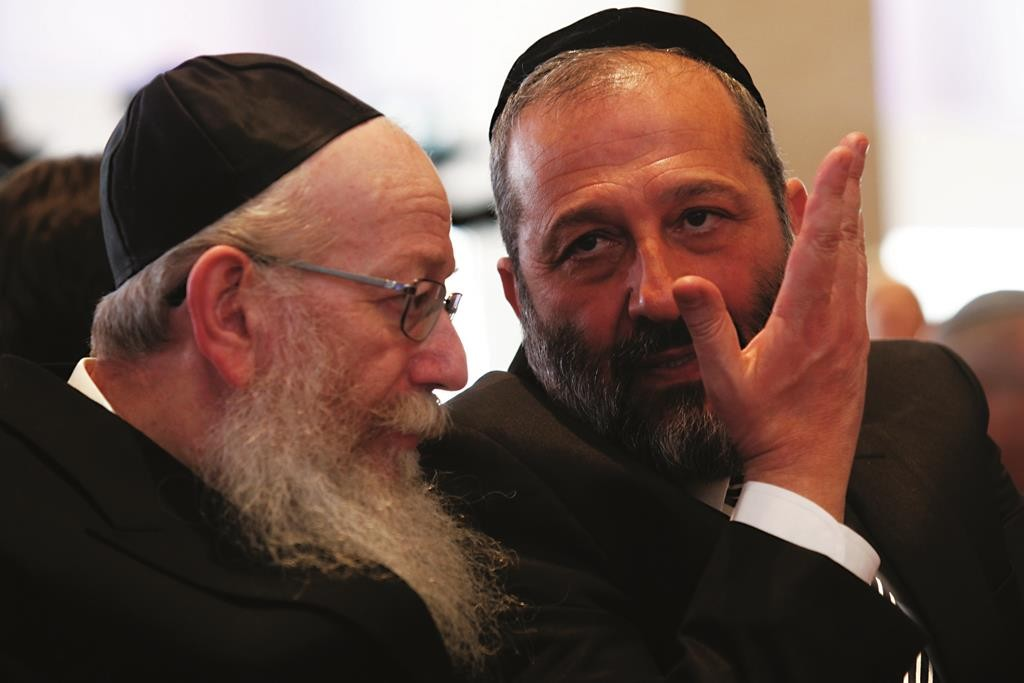 Leader of the 'Shas' party Aryeh Deri (R) speaks with leader o the United Torah Judaism party Yaakov Litzman during the opening session of the 20th Israeli parliament, held at the Knesset (Israeli parliament) on March 31, 2015. Photo by Nati Shohat/Flash90