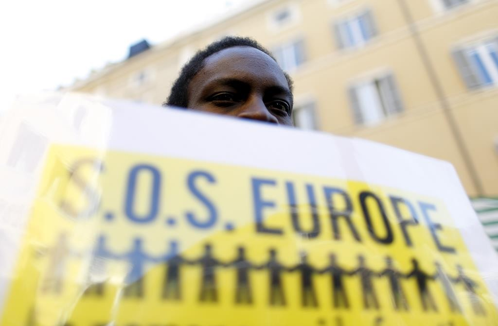 A migrant holds a placard during a protest in front of the Italian Chamber of Deputies in Rome, Tuesday. (REUTERS/Yara Nardi)