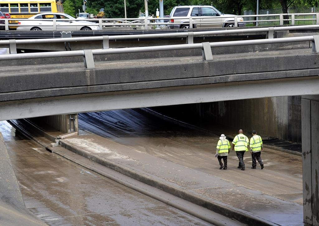 City of Houston workers walk along a wet, muddy, low stretch of Allen Parkway near downtown Houston, Wednesday. Heavy rains and flooding have kept the section closed to traffic.  (AP Photo/Pat Sullivan)