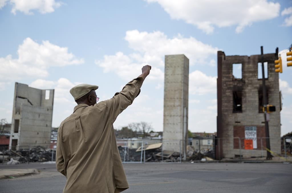 James Carter calls out to a friend crossing the street as he stands in front of the remains of a senior center that burned during the riots following Freddie Gray's funeral Sunday, in Baltimore. (AP Photo/David Goldman)