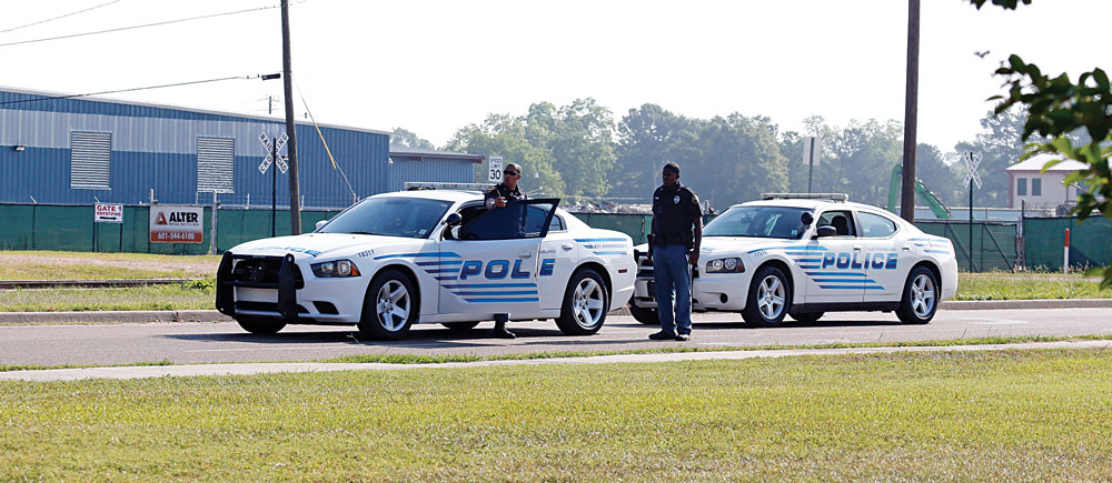 Two City of Hattiesburg police officers survey the site, Sunday morning, where an altercation began that left two Hattiesburg, Miss., police officers shot to death during a Saturday evening traffic stop.  (AP Photo/Rogelio V. Solis)