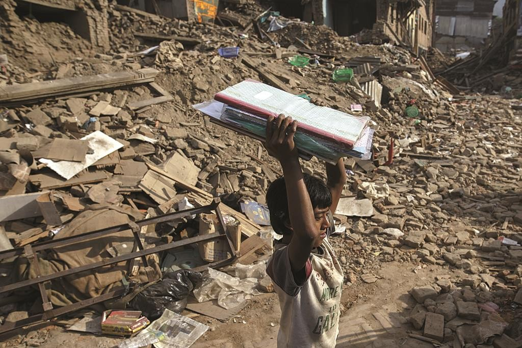 An earthquake survivor holds up salvaged belongings from his family's collapsed house in Sankhu, on the outskirts of Kathmandu, Nepal (REUTERS/Athit Perawongmetha)