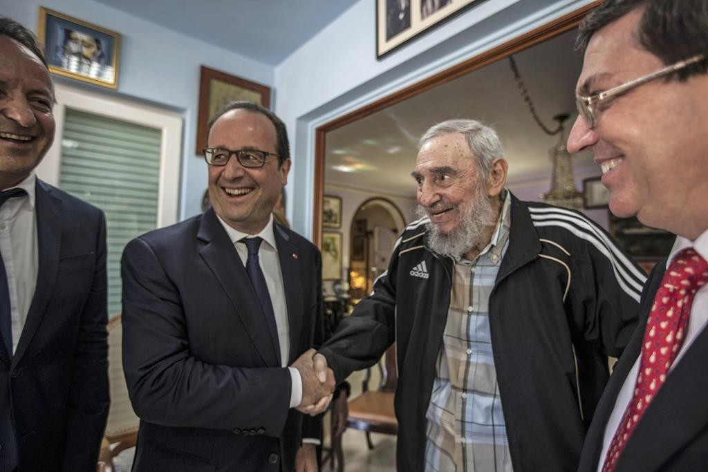 Cuba's former leader Fidel Castro, second right, shakes hands with French President Francois Hollande, while accompanied by Cuba's Foreign Minister Bruno Rodriguez, right, in Havana, Cuba, Monday. (AP Photo/Alex Castro)