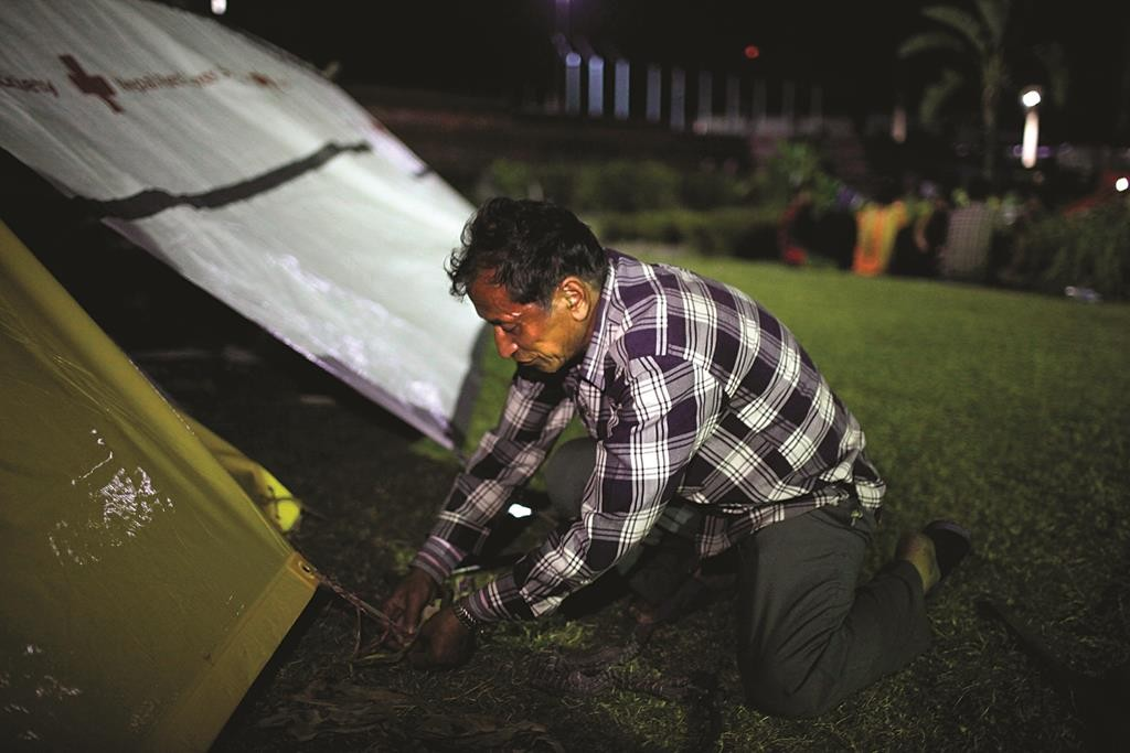 A Nepalese man adjusts his makeshift tent in an open space in Kathmandu, Nepal (AP Photo/Niranjan Shrestha)