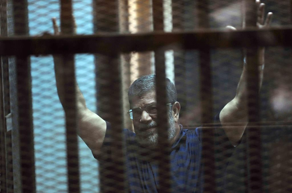 Ousted Egyptian President Mohammed Morsi raises his hands as he sits behind glass in a courtroom, in a converted lecture hall in the national police academy in an eastern Cairo suburb, Egypt, Saturday. (AP Photo/Ahmed Omar)