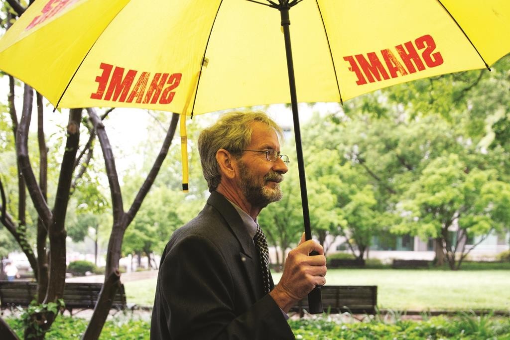 "Carrying an umbrella that says ""shame"" on it, Douglas Hughes of Florida arrives at federal court in Washington, Thursday. (AP Photo/Jacquelyn Martin)"