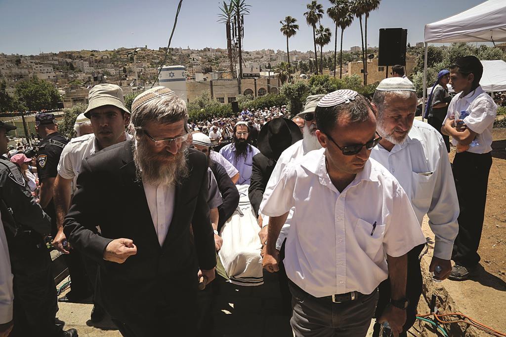 "Carrying the mitah of the niftar, z""l, at the levayah of Rabbi Moshe Levinger, in Kiryat Arba, Sunday. (Gershon ElinsonFlash90)"