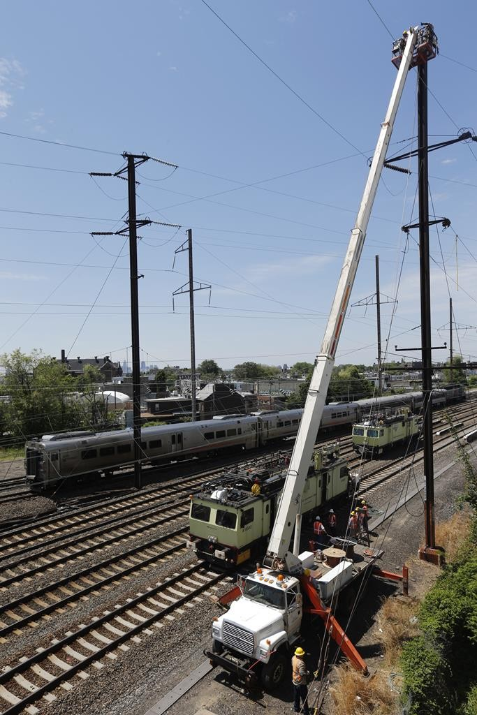 A New Jersey Transit train, back, rolls by as workers labor at the site where the deadly train derailment occurred. (AP Photo/Julio Cortez)