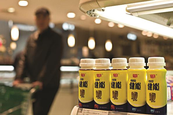 A man seen pushing a trolley past bottles of dairy products made by Bright Food Group in a supermarket in Shanghai. The company recently bought the controlling interest in Israel's largest food producer, Tnuva. (PHILIPPE LOPEZ/AFP/Getty Images)
