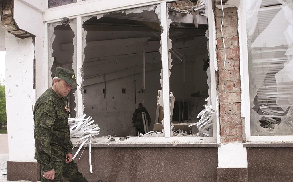 Eduard Basurin, deputy commander of the self-proclaimed Donetsk People's Republic, inspects a building that was recently damaged by shelling, in Donetsk, Ukraine. (REUTERS/Igor Tkachenko)